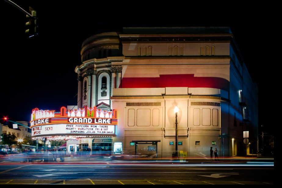 A movie theater at night with a brightly lit marquee