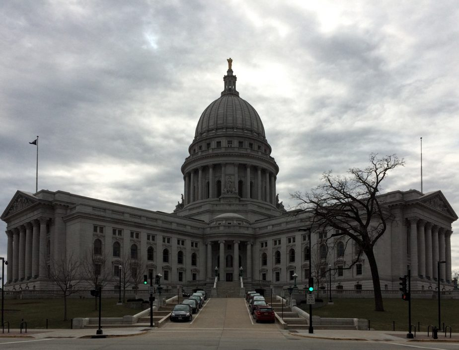 Wisconsin state capitol building looming beneath a cloudy sky