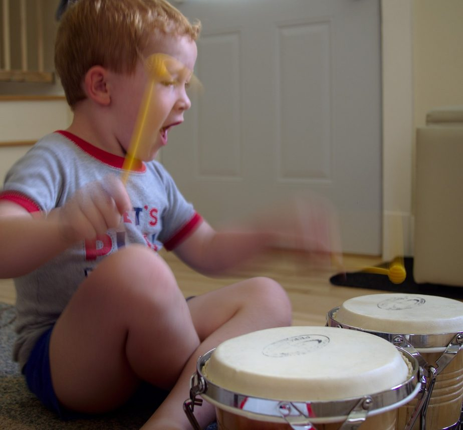 Young boy with open mouth drumming with fast moving drum sticks